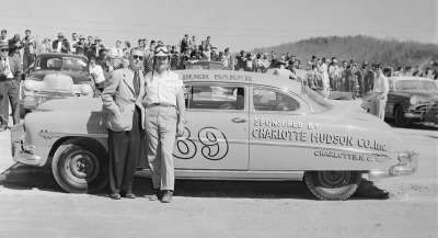Buck Baker stands beside his  #89 Hudson Hornet, which he drove in the April 12 NASCAR Grand National race.