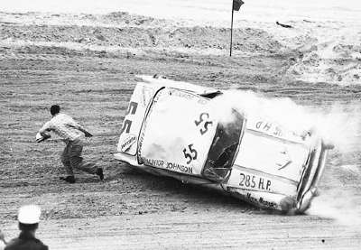 Junior Johnson climbed out of the rear window of his overturned Pontiac after a crash.