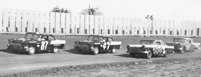 Number 87 Buck Baker and #47 Jack Smith wheel their Chevrolets around the lapped #154 Ford of Nace Mattingly.