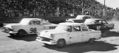 Number 98 Marvin Panch and #97 Paul Goldsmith slice their way through traffic during the 100-miler at North Wilkesboro Speed­way.