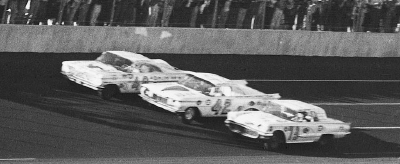 The cars of Weatherly, Petty, and Beauchamp approach the finish line in a three-abreast cluster.