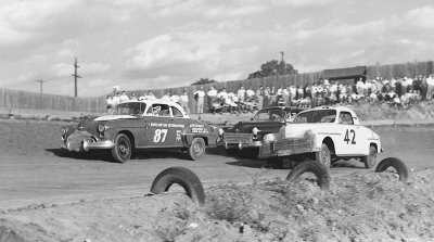 Buck Baker runs inches ahead of Lee Petty and Tim Flock during the Oct. 15, 1950 race at Martinsville Speedway.