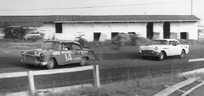 Fonty Flock cuts ahead of an unnumbered Buick on a dirt track during a 1955 NASCAR Grand National race.