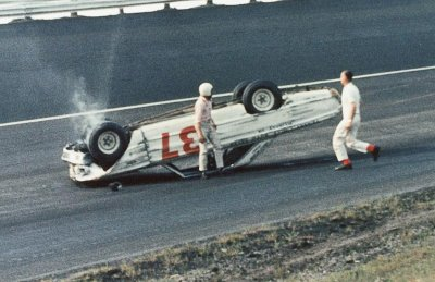 Bob Strickler climbs out of his overturned Ford after a crash in the May 8, 1965, Rebel 300 at Darlington.