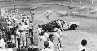 Ed Negre's #8 Ford is pushed into the pit after a collision in the 1968 Western North Carolina 500.
