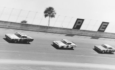 Joe Leonard, LeeRoy Yarbrough, and Buddy Baker throttle their way through the turn in the 1969 Firecracker 400.