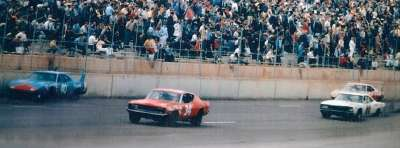 Pete Hamilton's #40 Plymouth Superbird passes #34 Wendell Scott and John Sears during the 1970 Alabama 500.