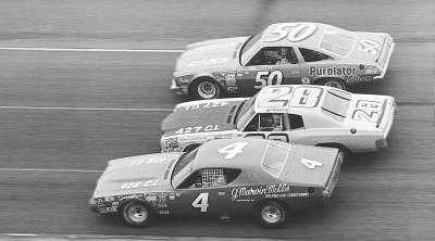 Number 4 John Sears, #28 Gordon Johncock, and #50 A.J. Foyt race in the 1973 Daytona 500.