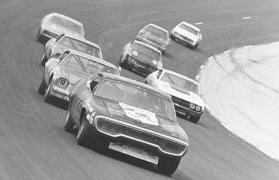 Dick Brooks' #22 Plymouth leads the charge off the fourth turn in the 1973 Talladega 500.