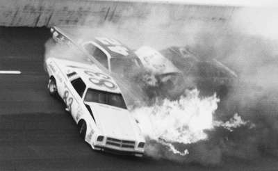 Flames erupt from the engine of Ramo Stott's #83 Chevrolet in the 1975 Winston 500.