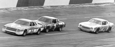 Number 11 Cale Yarborough leads #1 Donnie Allison, and #88 Darrell Waltrip in the Oct. 23, 1977 American 500.