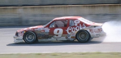 Smoke erupts from the #9 Coors Ford of Bill Elliott in the 1985 Winston 500.