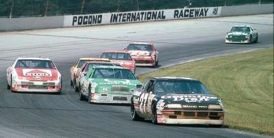 Number 27 Rusty Wallace leads  a hungry pack during the 1990 Miller Genuine Draft 500.