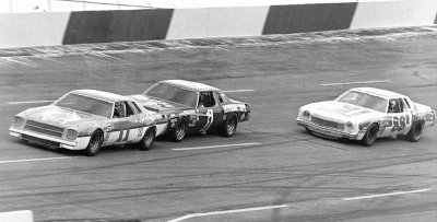 Number 11 Cale Yarborough, leads #1 Donnie Allison, and #88 Darrell Waltrip in the American 500 on Oct. 23, 1977.