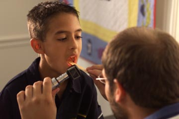 male doctor as he examines a patient's throat