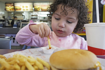A young girl eats some fries.