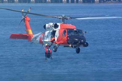 An HH-60 Jayhawk helicopter from Coast Guard Air Station Astoria, Ore., retrieves a rescue swimmer during a rescue pick-up drill.