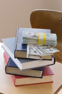 Stack of money laid on top of stack of books.