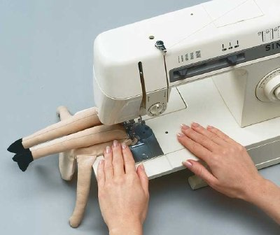 Use a sewing machine or needle and thread to seal in the stuffing in Henrietta witch's legs.