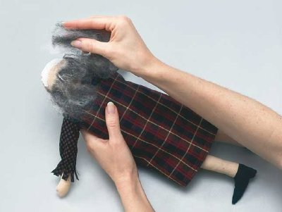 Use craft glue to attach wool roving to Henrietta witch for hair on this Halloween decoration.