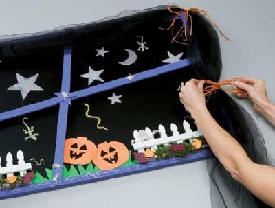 Tie the raffia at the sides to finish the creepy curtain for your window.