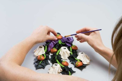 Use liquid clay to attach the last pumpkin to the middle of the bow.