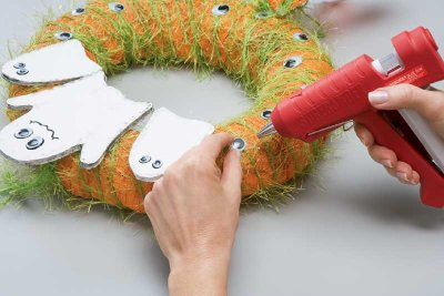 Use a hot glue gun to attach the ghosts to the wreath.