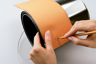 On the tangerine paper, mark where the knobs of the can's handles are.