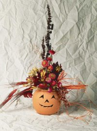 This Halloween decoration combines a terra cotta container with dried flowers to produce a floral jack-o'-lantern.