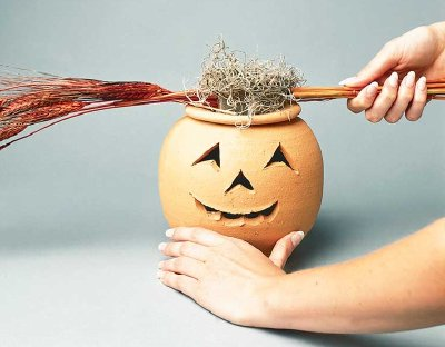 Moss and dried wheat provide the base for this floral jack-o'-lantern's display.