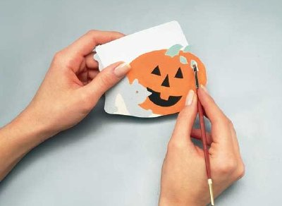 Use watercolor paper and paints to start making the ornament that will adorn your Halloween wreath.