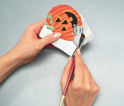 Use a floating brush technique to add detail to your Halloween wreath's ornament.