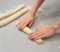 Gently roll the dough into a rope without using too much pressure when braiding challah.