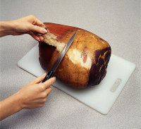 Slice away skin when roasting bone-in ham.