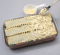 Sprinkle grated cheese evenly on top of the lasagna.