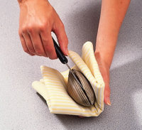 Use a towel or glove to secure the clam in your hand.