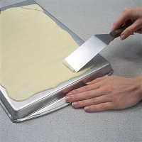 Push spatula along pan to make white chocolate curl.