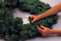 Shape the wreath by pulling out and fluffing up the branches.