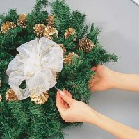 Use cloth-covered wire to secure the sheer white bow to the wreath.