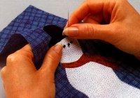 Stitch beads to eyes to finish Christmas vest.
