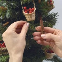 Attach the cinnamon sticks to the tree between the baskets.