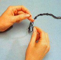 Tie a square knot around the seed bead to make hematite and gold necklace.