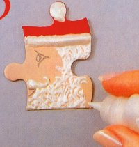 Dry white lines for Santa's beard on Santa-themed puzzle pin to make Christmas jewelry.