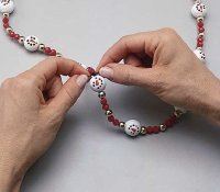 Tie string ends into a double knot to make snowmen jewelry.