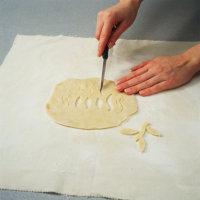 Cut out decorative designs with a paring knife when making pretty pie crust cutouts for pastries.