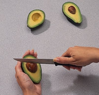 Lodge the knife blade inside the avocado pit and pull it free.