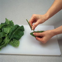 Fold the spinach leaf in half and gently tear off the stem.