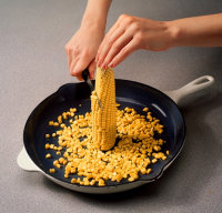 Stand the cob on end and cut down the sides, releasing the kernels.