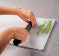 Slice beans lengthwise on a cutting board.