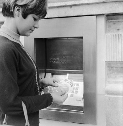 A woman withdraws money from the first cashpoint machine in London, in 1967.